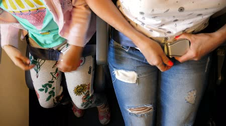 necessity : top view. Close up of female and kid hands fastening, buckle up the cabin seat belt while sitting on airplane seat for safety flight . Safety travel concept Stock Footage