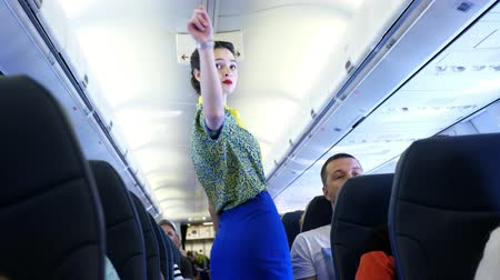 attendant : AIRPORT BORYSPIL, UKRAINE - OCTOBER 24, 2018: Ukraine International Airlines. Flight attendant, stewardess gives preflight instructions, during Pre-flight safety demonstration. Interior of airplane with passengers on seats