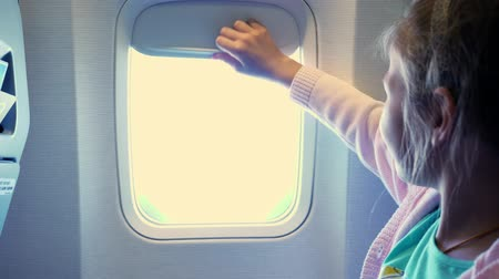 elevação : close-up. kid girl raises the porthole curtain in the airplanes cabin, from there shines a bright light. girl looking out through airplanes window viewing Sky and Clouds and landscape below Stock Footage