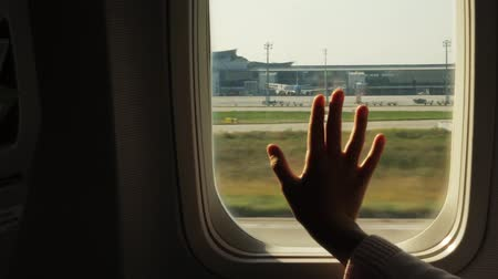 forefinger : Kid s hand touching airplane window, close up. Silhouette of a childs palm against the background of a window in an airplane. The concept of safety of flights.