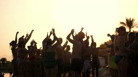 crowd together : dark silhouettes of people dancing, having fun on the beach, in summer, at sunset. Beach party Stock Footage
