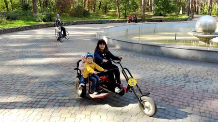 triciclo : CHERKASY, UKRAINE, OCTOBER 17, 2018: mother with young children riding a big tricycle, in the autumn park. warm autumn sunny day.