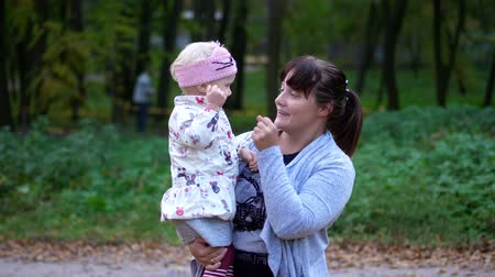 eskimo : CHERKASY, UKRAINE, OCTOBER 17, 2018: mom plays with her small, pretty two-years-old daughter, hugging her, walking with her in an autumn park. warm autumn sunny day.