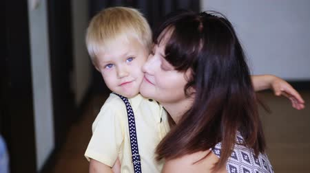 átölelő : CHERKASY, UKRAINE, OCTOBER 17, 2018: portrait, mother hugs tightly, with love, her little son, a blond boy of 4 years.