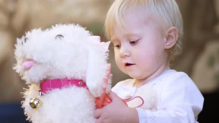 pelyhes : CHERKASY, UKRAINE, OCTOBER 17, 2018: little, blond girl of 2 years old, in a beautiful dress, playing with a toy dog,