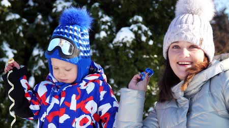 fete : CHERKASY REGION, UKRAINE, DECEMBER 25, 2018: winter, frosty, snowy, sunny day. happy family, mother with small children throw up multi-colored tinsel and confetti, outdoors, having fun. Stock Footage