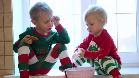 finomságok : CHERKASY REGION, UKRAINE, DECEMBER 25, 2018: family new year, christmas. Little blond children are wearing Christmas costumes. they eat various goodies and sweets. Stock mozgókép