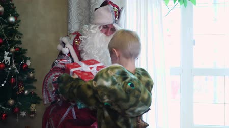 gruta : CHERKASY REGION, UKRAINE, DECEMBER 25, 2018: family new year, christmas. family with small children dressed in Christmas costumes. Santa Claus visits children. they have fun together, get presents