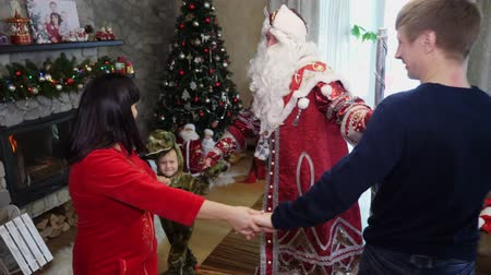 kulübe : CHERKASY REGION, UKRAINE, DECEMBER 25, 2018: family new year, christmas. family with small children dressed in Christmas costumes. Santa Claus visits children. they have fun together, get presents