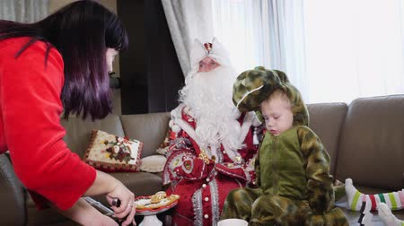 juntar : CHERKASY REGION, UKRAINE, DECEMBER 25, 2018: family new year, christmas. family with small children dressed in Christmas costumes. Santa Claus visits children. they have fun together, get presents
