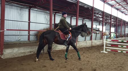 lő : in special hangar, a young disabled man learns to ride a black, thoroughbred horse, hippotherapy. man has an artificial limb instead of his right leg. concept of rehabilitation of disabled with animals.
