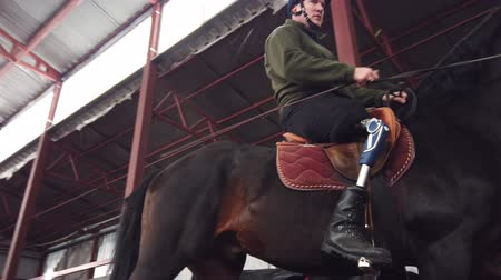 positive vibes : in special hangar, a young disabled man learns to ride a black, thoroughbred horse, hippotherapy. man has an artificial limb instead of his right leg. concept of rehabilitation of disabled with animals.