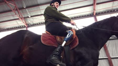 インストラクター : in special hangar, a young disabled man learns to ride a black, thoroughbred horse, hippotherapy. man has an artificial limb instead of his right leg. concept of rehabilitation of disabled with animal