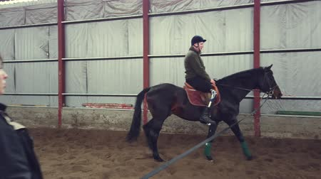 rehabilitasyon : in special hangar, a young disabled man learns to ride a horse with close supervision teacher, hippotherapy. man has artificial limb instead of his right leg. rehabilitation of disabled with animals.
