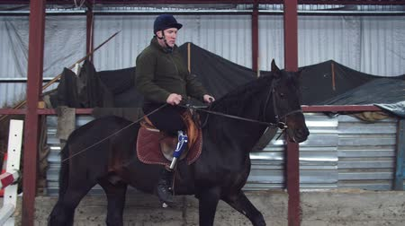 therapeutic : in special hangar, a young disabled man learns to ride a black, thoroughbred horse, hippotherapy. man has an artificial limb instead of his right leg. concept of rehabilitation of disabled with animals.