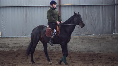 hippo : in special hangar, a young disabled man learns to ride a black, thoroughbred horse, hippotherapy. man has an artificial limb instead of his right leg. concept of rehabilitation of disabled with animals.