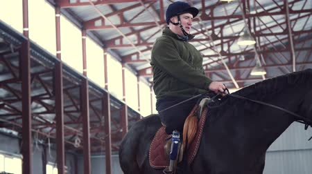 hippos : in special hangar, a young disabled man learns to ride a black, thoroughbred horse, hippotherapy. man has an artificial limb instead of his right leg. concept of rehabilitation of disabled with animals.
