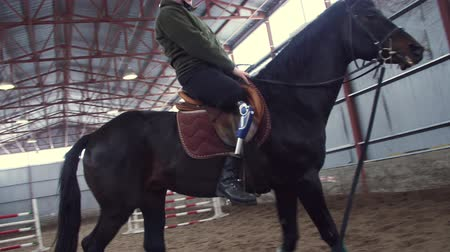prosthesis : in special hangar, a young disabled man learns to ride a black, thoroughbred horse, hippotherapy. man has an artificial limb instead of his right leg. concept of rehabilitation of disabled with animals.