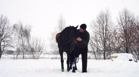 amputee : winter, disabled man stands near black horse on snowy field. man strokes a muzzle of a horse. man has prosthesis instead of his right leg. he learns to ride horse, hippotherapy. rehabilitation of disabled with animals.