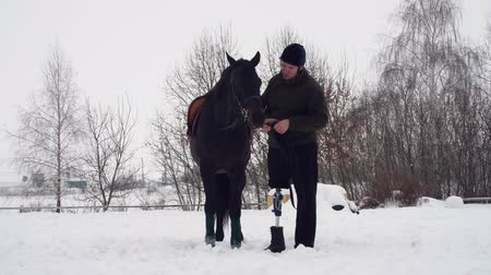 hippo : winter, disabled man stands near black horse on snowy field. man strokes a muzzle of a horse. man has prosthesis instead of his right leg. he learns to ride horse, hippotherapy. rehabilitation of disabled with animals.