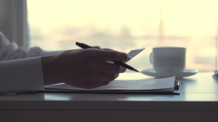 księgowa : close-up, female hand, holding a black pen and writing something in documents, business woman working with graphs and diagrams, on a white desktop in the office. Wideo