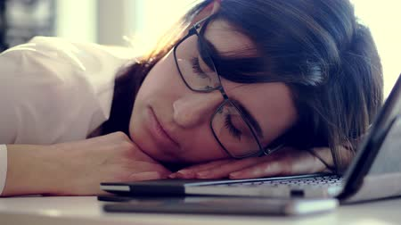 houding : Overworked, Exhausted and tired young businesswoman with glasses, resting, sleeping over a laptop in a desk at work in her office. she is overwhelmed by work, portrait shot Stockvideo