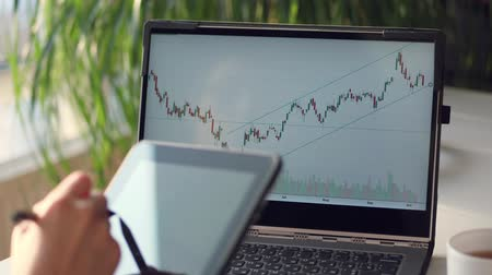 holding document : close-up. against the background of a laptop monitor with graphs. womens hands write something in the tablet. Businesswoman analyzing financial data on tablet and computer screen. Stock Footage
