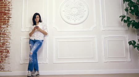 estuque : Full length portrait of young woman, girl, brunette, in white shirt and jeans, standing on background of white wall with decorative stucco, with smartphone. looks at screen, typing something in a smartphone Stock Footage