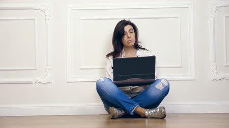 estuque : Full length portrait of young woman, girl, brunette, in white shirt and jeans, working on laptop computer while sitting on floor with legs crossed, on background of white wall with decorative stucco,