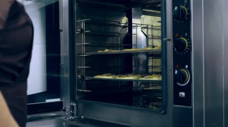 grzejnik : close-up, the cook puts in a large industrial oven, a baking tray with buns, pizza made with yeast dough, for baking, cooking. Baking bread in industrial restaurant kitchen, bakery using commercial oven
