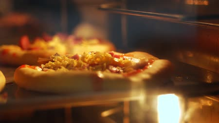 espargos : close-up, the process of baking mini pizza from yeast dough in a large industrial oven. Baking bread in an industrial restaurant kitchen or bakery using a commercial oven.