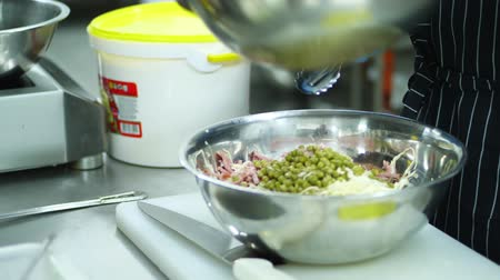 tudo : close-up, cooking vegetable salad with mayonnaise in a metal bowl, salad bowl. the cook mixes all the ingredients, puts a few spoons of mayonnaise, and peppers.
