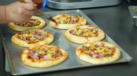 fast food : close-up, the process of cooking several mini pizza from yeast dough, with sausage and cheese. Chef sprinkles pizza with cheese. process of cooking bakery, in mess hall, resturant. Stok Video