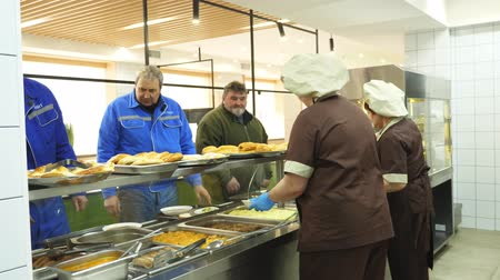 caixa : CHERKASY, UKRAINE, FEBRUARY 20, 2019: showcase with dishes in modern canteen, cafeteria, mess hall. factory employees having lunch in the canteen, people are Served Meals In factory Canteen. Vídeos