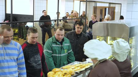 tray : CHERKASY, UKRAINE, FEBRUARY 20, 2019: showcase with dishes in modern canteen, cafeteria, mess hall. factory employees having lunch in the canteen, people are Served Meals In factory Canteen. Stock Footage