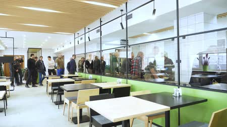 посылка : CHERKASY, UKRAINE, FEBRUARY 20, 2019: bright, spacious mess hall, people stand in line near showcases with dishes in modern canteen, cafeteria, mess hall. factory employees having lunch in the canteen,