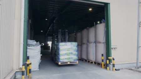 stockpile : Forklift driver stacking corn large pack pallets with by stacker loader, takes pallets away, transports them from a large warehouse of agricultural company. Stock Footage