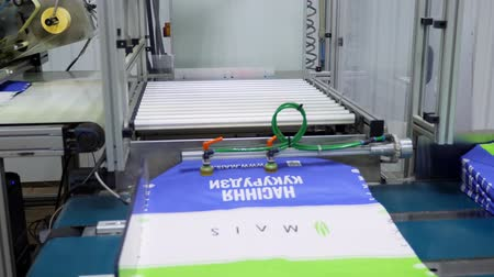 livraria : UKRAINE, CHERKASY, MARCH 25, 2019: agricultural company MAIS. Close up, already printed packages for grain, corn, agricultural products on conveyor belt. printing Press, process in the workshop