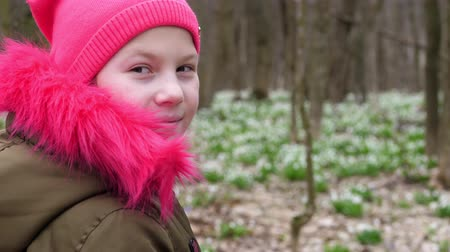 caqui : Portrait of a teenager girl in a bright pink hat and a khaki-colored jacket with bright pink fur against the background of blooming snowdrops, in the spring forest