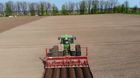 palánták : UKRAINE, CHERKASY, MAY 5, 2019: aerial survey, large tractor with special equipment rides through plowed field of black soil, forms even rows for mechanized machine potatoe planting . planting season, . fine spring day Stock mozgókép