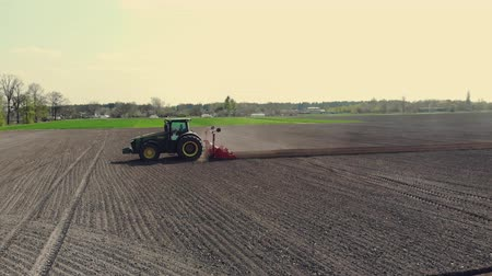 sow : UKRAINE, CHERKASY, MAY 5, 2019: aerial survey, large tractor with special equipment rides through plowed field of black soil, forms even rows for mechanized machine potatoe planting . planting season, . fine spring day Stock Footage