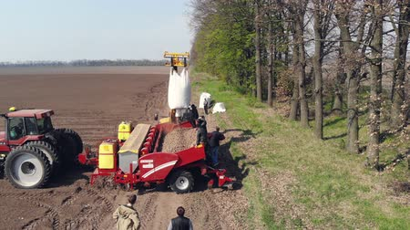 ekili : UKRAINE, CHERKASY, MAY 5, 2019: aerial survey, top view, potato seeds, potatoes are poured into the back of the tractor, process of mechanized machine potatoe planting in the field . spring day, planting season.
