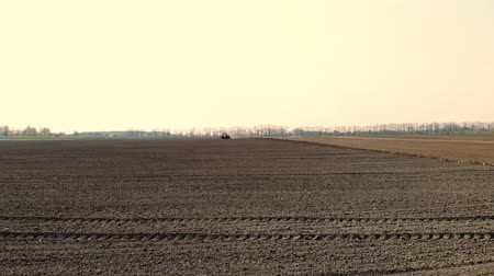 tillage : aerial survey, a large tractor rides through a plowed field of black soil, raising a cloud of dust behind it. planting season. planting potatoes. fine spring day Stock Footage