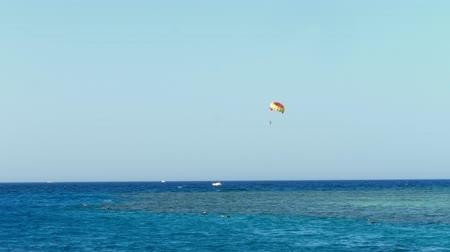 volleyball : Parachute from kitesurfing hovers over the waters edge against the clear blue sky. summer, seascape. water surface, quiet calm turquoise sea and blue sky. vacationers swim with masks for snorkeling in sea. view from the beach to the sea.