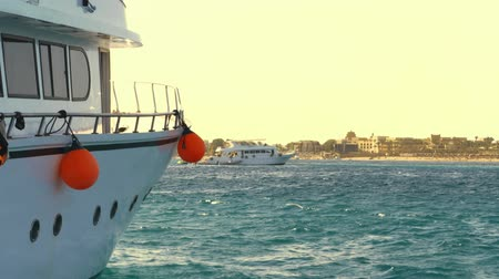fender : sea day landscape, yachts go to the bay, anchor. close-up, white yachts board with Yachting, sailing conept. Sailboat in the sea with many red fenders orange buoys. Stock Footage