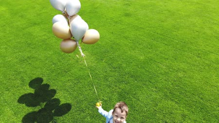 torcendo : aerial video, top view, at the stadium, in the center of a green football field, happy boy with balloons is runing through the football field. spring sunny day.