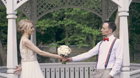 szörnyszülött : a young beautiful couple are standing in the gazebo, opposite each other and passing each other a wedding bouquet, fooling around, smiling. spring sunny day. wedding Stock mozgókép