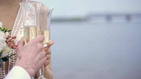 házasodik : close-up, newlyweds are holding champagne glasses . against the background of blue sea and sky. spring sunny day. wedding Stock mozgókép