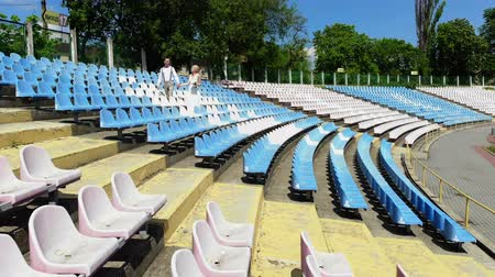 cíle : aerial video, at the stadium, newlyweds in wedding attire are walking between the white and blue seats . spring sunny day. wedding