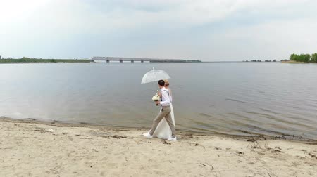 новобрачный : aero, beautiful newlyweds walking along the beach, under a transparent umbrella, against the blue sky, river, and a large bridge over the river. spring sunny and a little bit rainy day. wedding